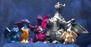 The lineup of my evolution of dragon sculptures (and a friend of the family).  From left to right: Gargoyle, Orange Cat, Missing Link, Kangaroo, Big Guy, Prototype